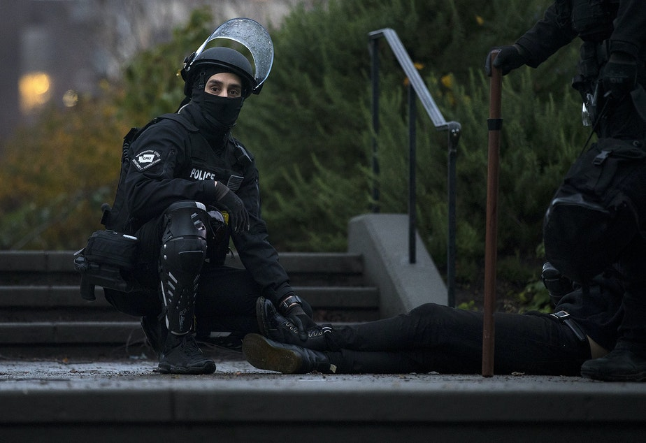 caption: A Seattle police officer holds down the feet of an individual who was arrested during the sweep of unhoused community members at Cal Anderson Park  on Friday, December 18, 2020, in Seattle.