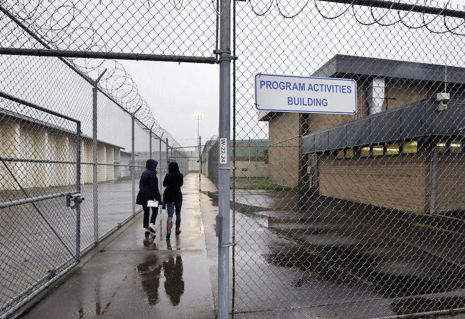 caption: FILE: In this photo taken Thursday, Jan. 28, 2016, staff members head past razor wire-topped fences and into a building hosting a University Behind Bars program at the Monroe Correctional Complex in Monroe, Wash.