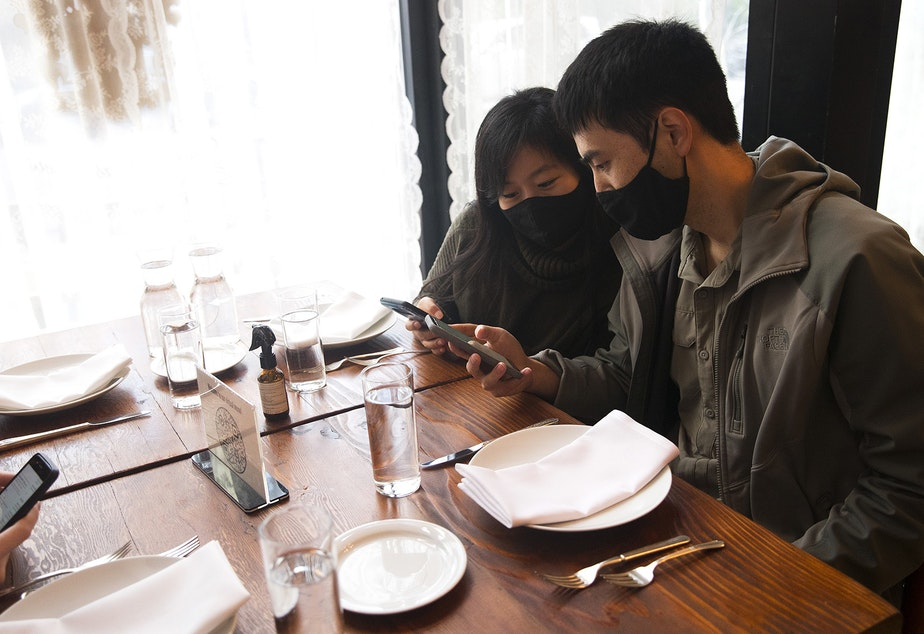caption: Julie Ding and James Che, right, look at a QR code menu on their phones before ordering on Wednesday, October 21, 2020, at Spinasse on Capitol Hill in Seattle.