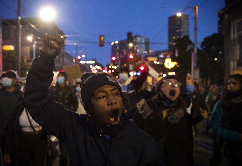 caption: Organizer TK leads a group of people protesting for racial justice and against police brutality back to the Capitol Hill Organized Protest zone from the Seattle Police Department's West Precinct building on the 18th day of protests following the murder of George Floyd, on Tuesday, June 16, 2020, in Seattle.