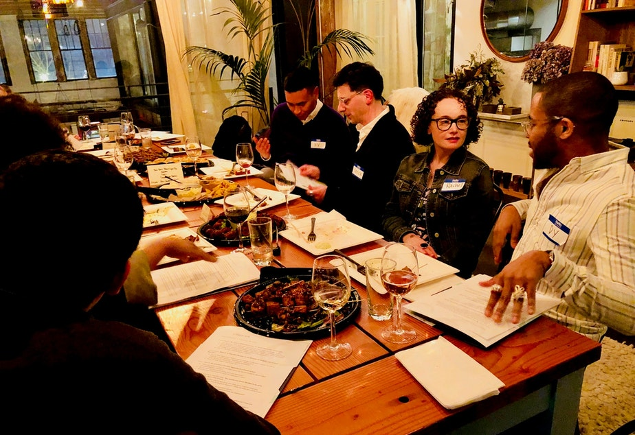 caption: Dy Johnson and Rachel Oppenheim talk over dinner at KUOW's first Pop-Up Curiosity Club on February 28, 2019 at The Cloud Room in Seattle. Patrick Holderfield and Uly Rivera chat in the background.