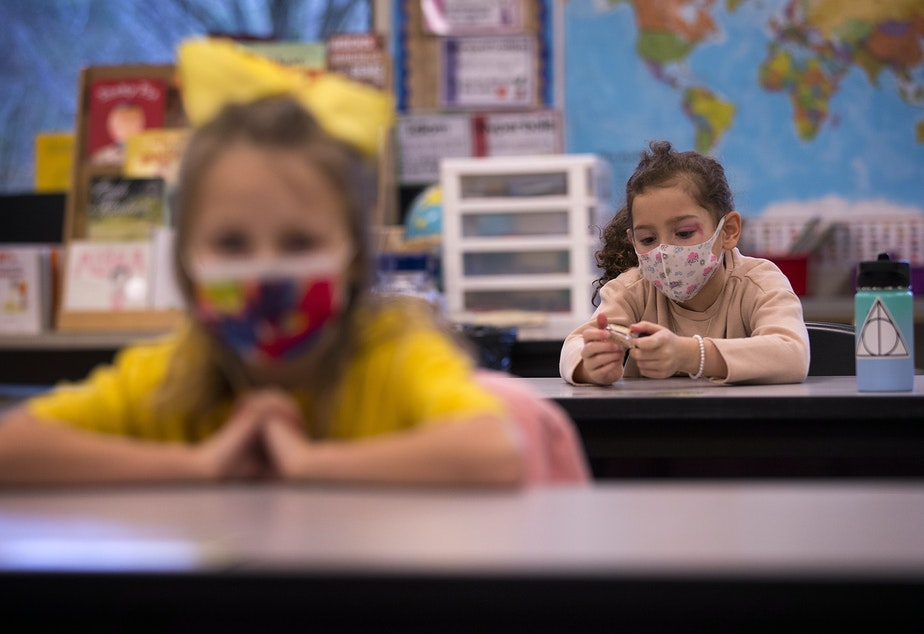 caption: Second-grade student Nelly, right, plays with a bottle of hand sanitizer at her desk on Thursday, January 21, 2021, as second-grade students returned to in-person learning at Somerset Elementary School in Bellevue.