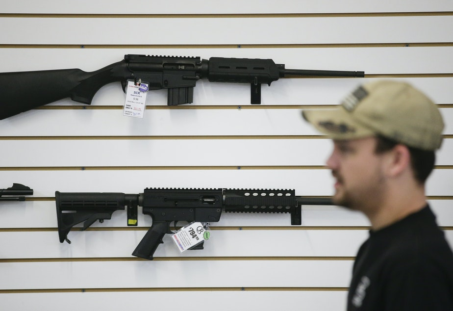 caption: In this Dec. 9, 2015, photo, a sales associate walks past semiautomatic rifles at Bullseye Sport gun shop in Riverside, Calif.