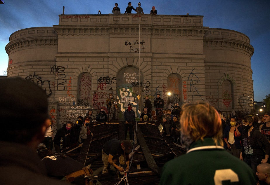 caption: A crowd gathers around a Black Power fist art instillation during an attempt to lift the structure inside the Capitol Hill Organized Protest Zone on Tuesday, June 16, 2020, in Seattle. As a result of safety concerns, the group decided to lift the heavy structure the following day instead.