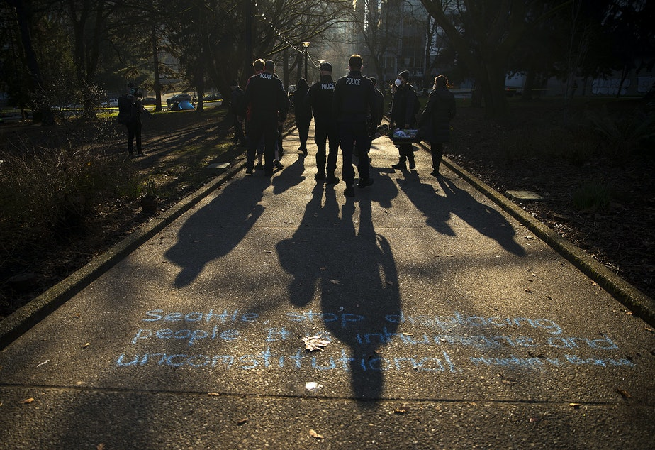 caption: Seattle police officers walk over chalk writing that reads 'Seattle, stop displacing people. It is inhumane and unconstitutional. Martin v. Boise,' before sweeping unhoused people from Denny Park on Wednesday, March 3, 2021, in Seattle.