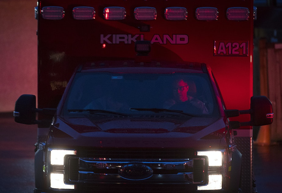 caption: Members of the Kirkland Fire Department arrive at the Life Care Center of Kirkland on Monday, March 2, 2020, to transport a patient to the hospital.
