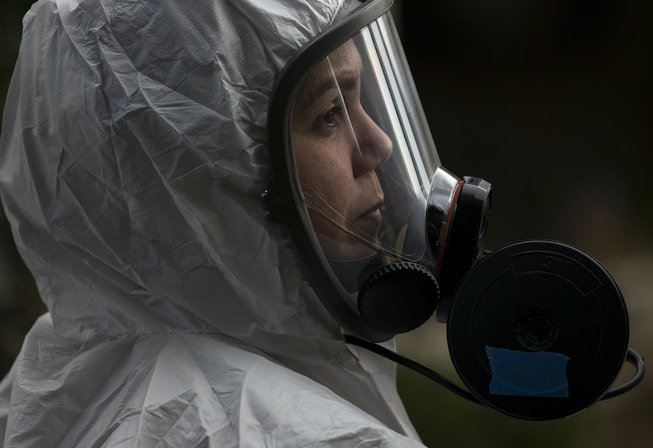 caption: A member of a Servpro cleaning crew stands in line before entering the Life Care Center of Kirkland, the long-term care facility at the epicenter of the coronavirus outbreak in Washington state, on Wednesday, March 11, 2020, in Kirkland.