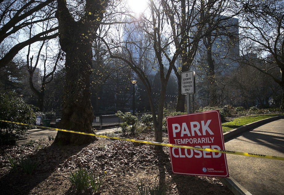 caption: A 'Park Temporarily Closed' sign is shown as Seattle police and Parks and Recreation sweep unhoused people from Denny Park on Wednesday, March 3, 2021, in Seattle.