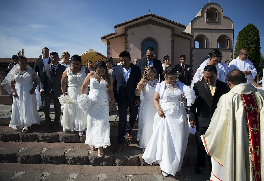 caption: Couples walk to have a group photograph taken on the steps of the church before a mass wedding ceremony with 23 couples on Sunday, June 2, 2019, at Our Lady of the Desert Church in Mattawa.