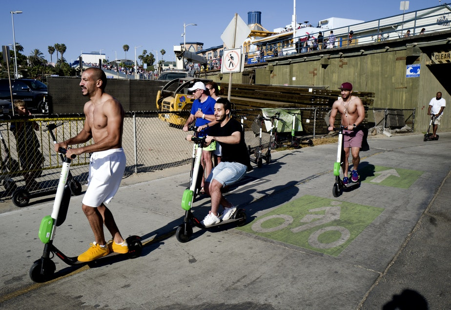 In this July 1, 2018 photo people ride Lime and Bird scooters along the strand in Santa Monica, Calif.