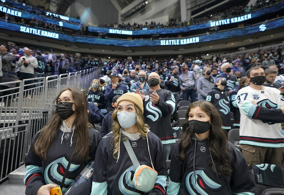 caption: Seattle Kraken fans watch in Climate Pledge Arena as players warm up Saturday, Oct. 23, 2021, in Seattle, for the NHL hockey expansion team's home-opener against the Vancouver Canucks.