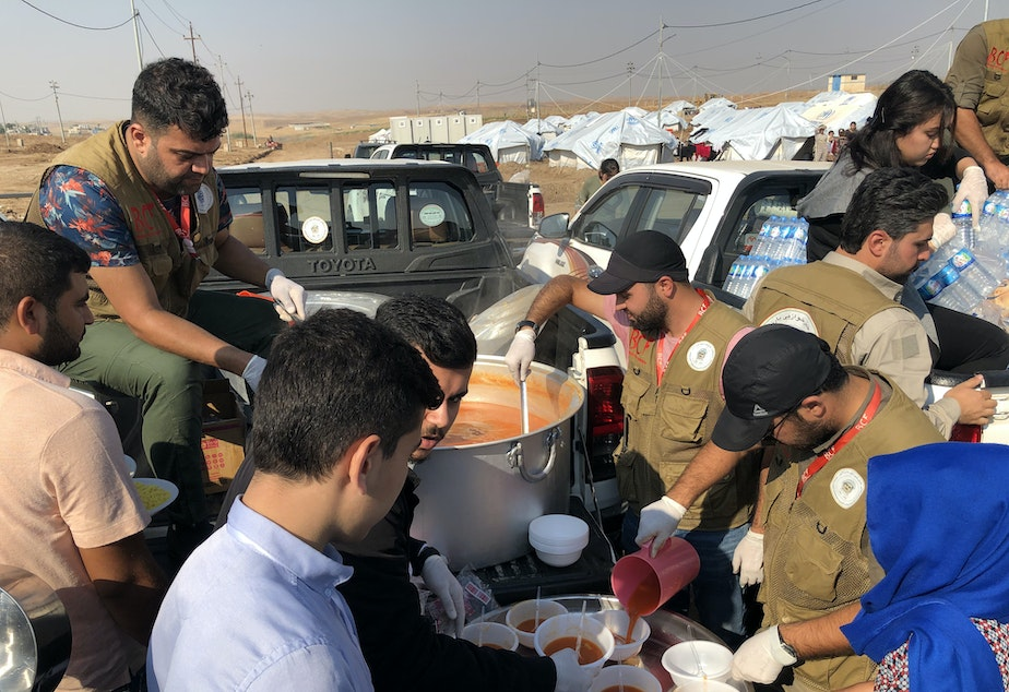 caption: Aid workers dish up rice and stew to refugees at the Gawilan camp in northern Iraq. The camp has accommodated nearly 2,000 new arrivals in the past month.