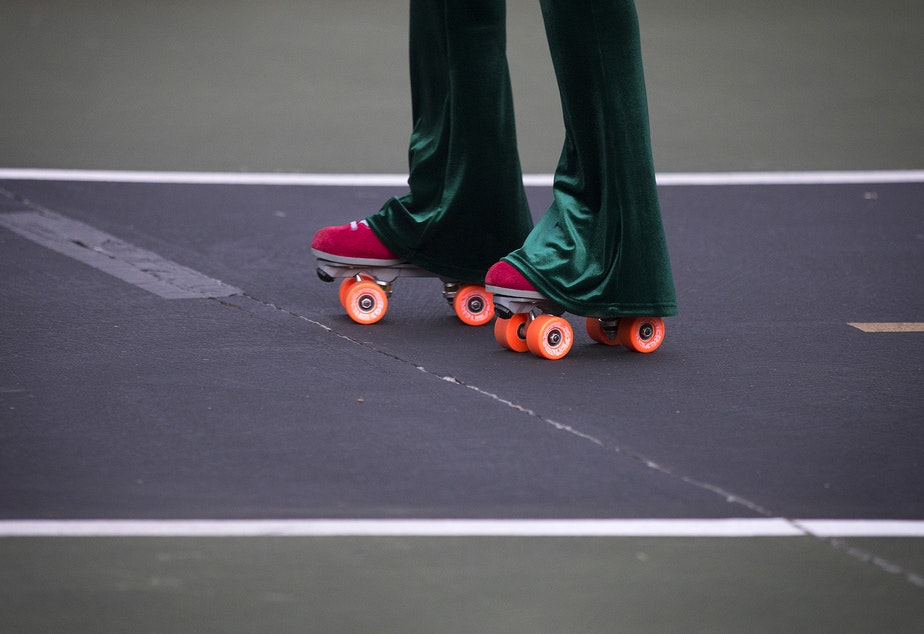 caption: Vanessa Poston roller-skates during a decades themed skate meet up on Tuesday, October 6, 2020, at the White Center Bicycle Playground in Seattle.