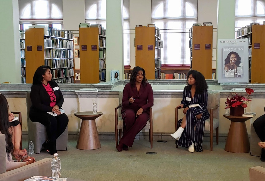 caption: Former First Lady Michelle Obama meets with the Balanced Black Girl Book Club at the Tacoma Public Library on Sunday, March 24, 2019.