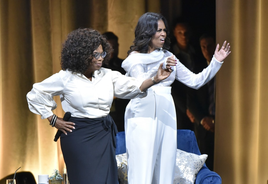 "Michelle Obama, right, is greeted by Oprah Winfrey to discusses her new book during an intimate conversation to promote ""Becoming"" at the United Center on Tuesday, Nov. 13, 2018, in Chicago."