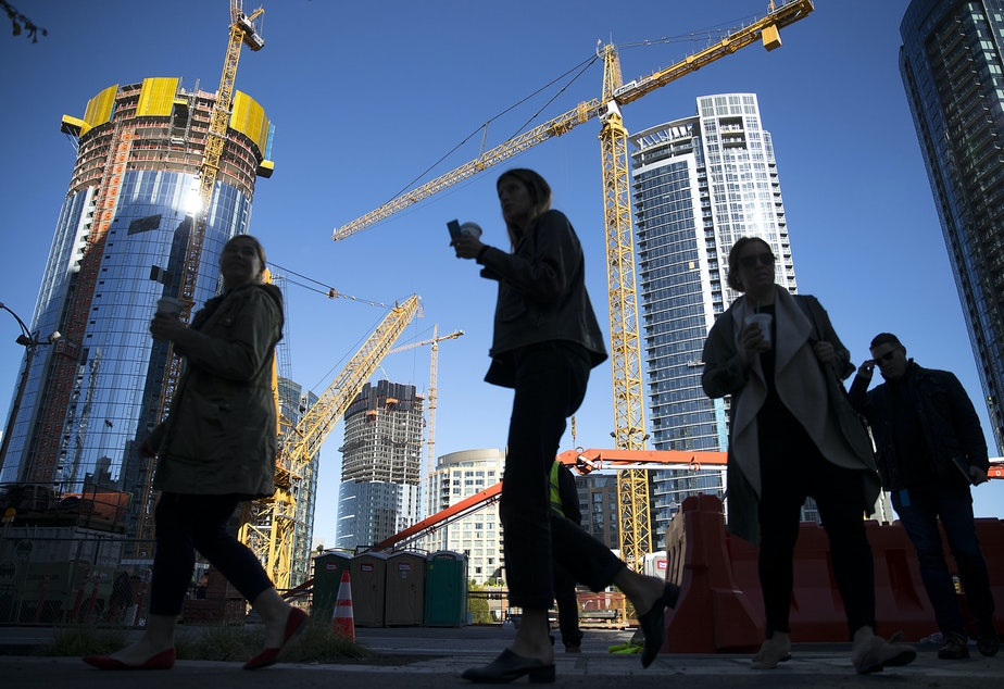 People walk on 7th Ave., in front of construction and cranes on Tuesday, October 24, 2017, in Seattle.