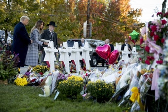 First lady Melania Trump, accompanied by President Donald Trump, and Tree of Life Rabbi Jeffrey Myers, right, places a white flower at a memorial for those killed at the Tree of Life Synagogue in Pittsburgh, Tuesday, Oct. 30, 2018. (AP Photo/Andrew Harnik)