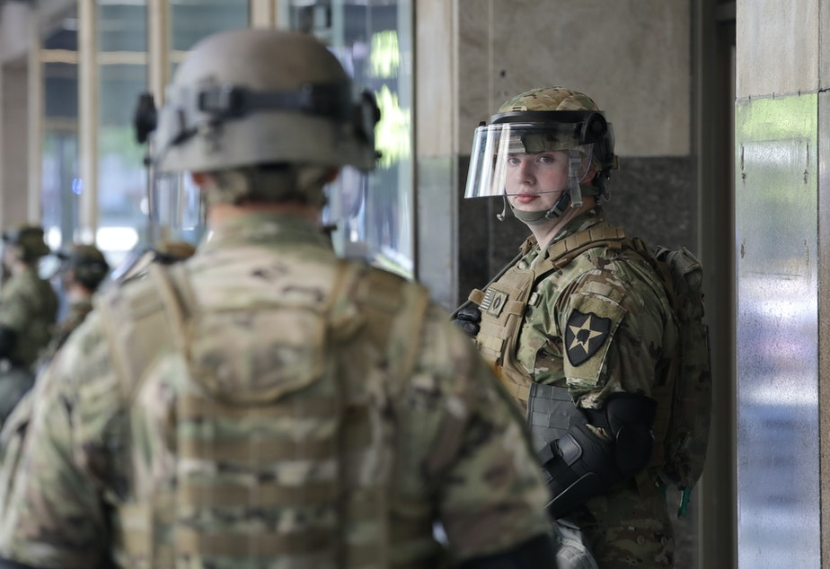 caption: A Washington National Guard soldier looks across at another as they stand guard outside a previously closed Macy's department store as a protest begins nearby Monday, June 1, 2020, in Seattle, following protests over the weekend over the death of George Floyd, a black man who was in police custody in Minneapolis.