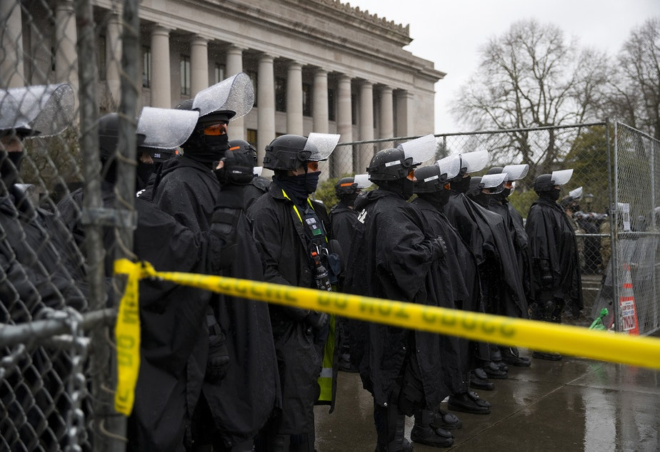 caption: Police guard the Washington State Capitol on Monday, January 11, 2021, as a handful of protesters gathered on the opposite side of the fence on the first day of the legislative session in Olympia.