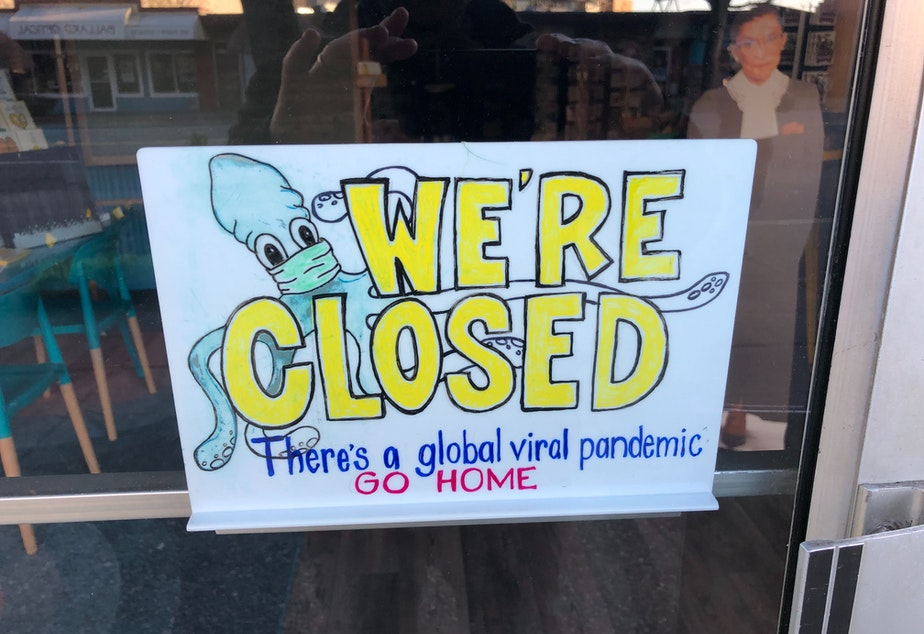 caption: A sign in the door of a Ballard cafe, March 16, 2020 amid statewide orders to stay home and practice social distancing in response to the COVID-19 outbreak.
