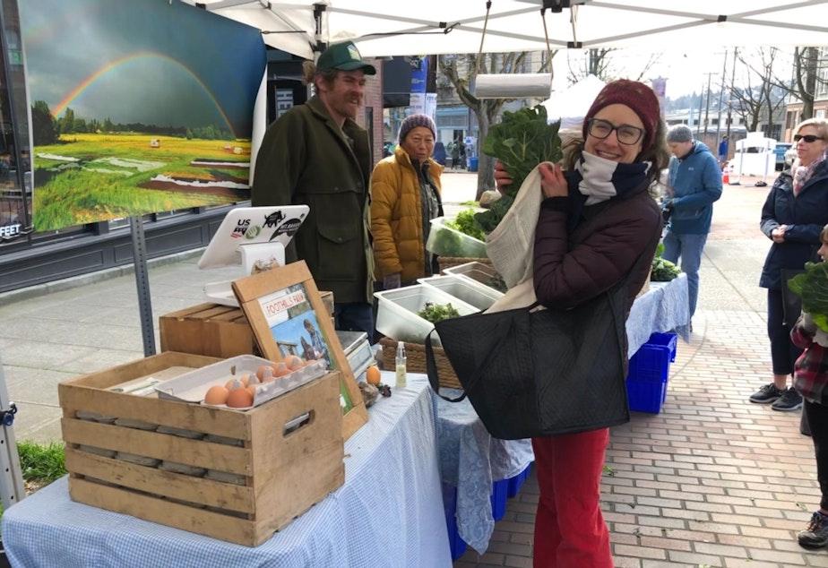 caption: Mary Purdy buys produce at the Sunday Farmers Market in Ballard from Foothills Farm's Matt Steinman.