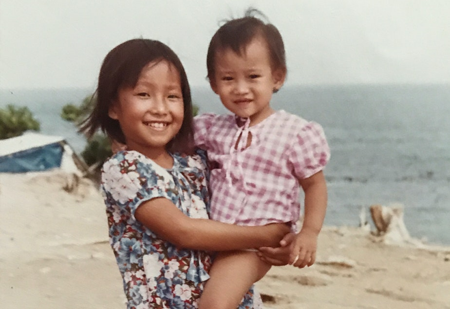 caption: Eight-year-old Diem Pham holds her 1-year-old cousin Kim Pham at a refugee camp in Malaysia in May 1980.