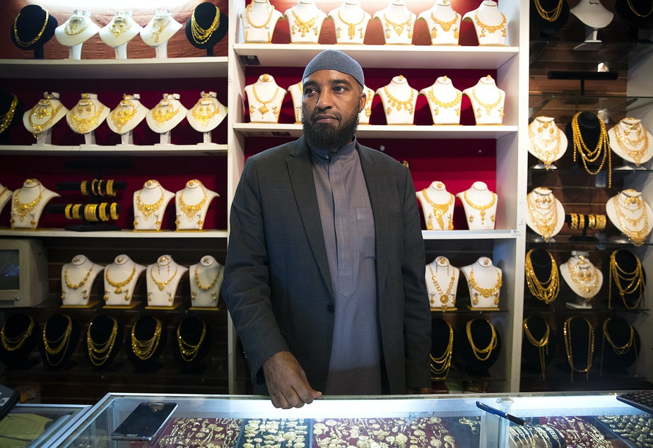 Ali Jama stands behind the counter of Haveniceday Jewelry on Thursday, April 19, 2018, in Tukwila.