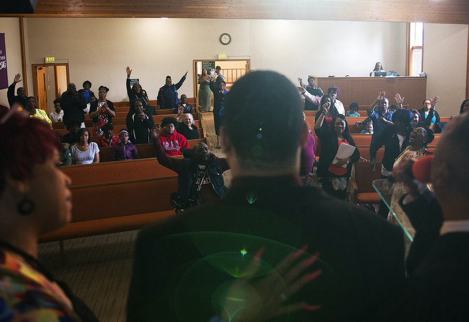 caption: DaShawn Horne stands on stage with Bishop Zachary Bruce and his mother, LaDonna Horne, on Sunday, May 19, 2019, at Freedom Church of Seattle. The night before, DaShawn was in the emergency room after suffering a seizure. On stage, DaShawn repeated 'praise god' into the microphone after Bishop Bruce introduced him as his miracle man.
