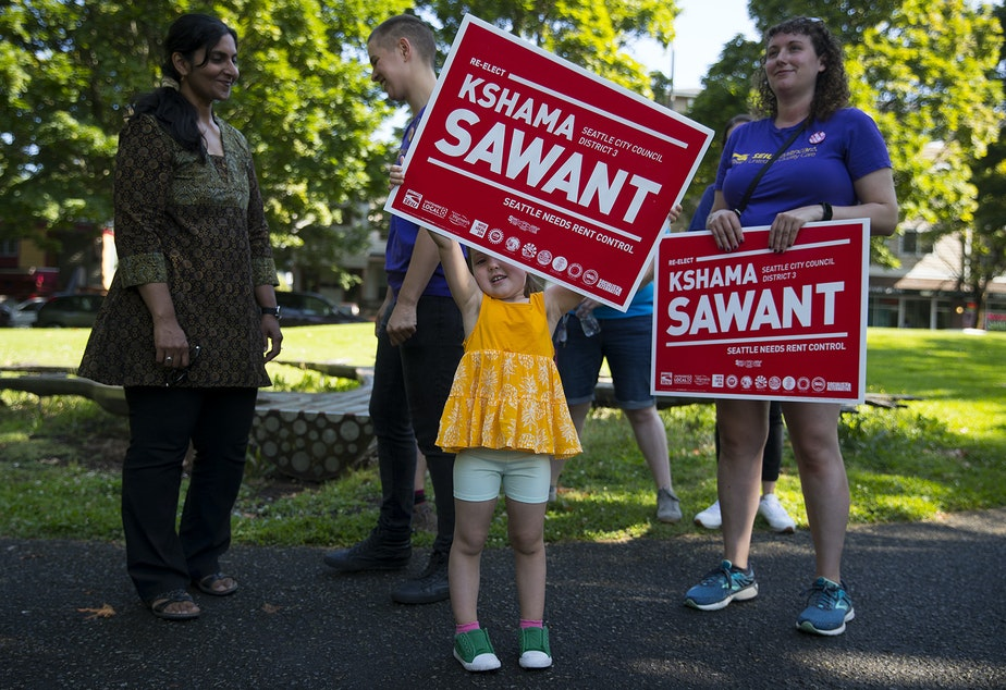 Everett Haggard-Mlynarek, holds a sign supporting councilmember Kshama Sawant before knocking on doors on Sunday, August 4, 2019, at Pratt Park in Seattle.