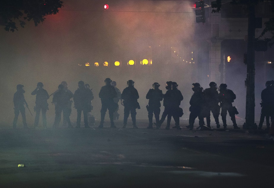 caption: Seattle police officers dressed in riot gear stand in a cloud of tear gas, pepper spray and flash grenade smoke on the fifth day of protests following the violent police killing of George Floyd on Tuesday, June 2, 2020, at the intersection 11th and Pine Street in Seattle.