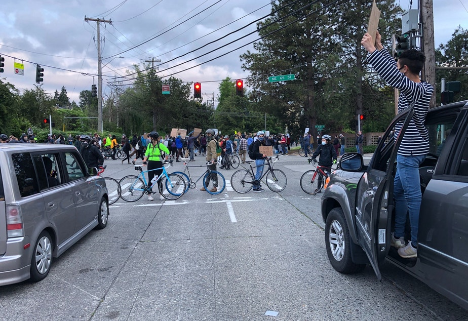caption: Bicyclists block an intersection as people march between Magnuson Park and University Village in Seattle on Saturday, June 6.