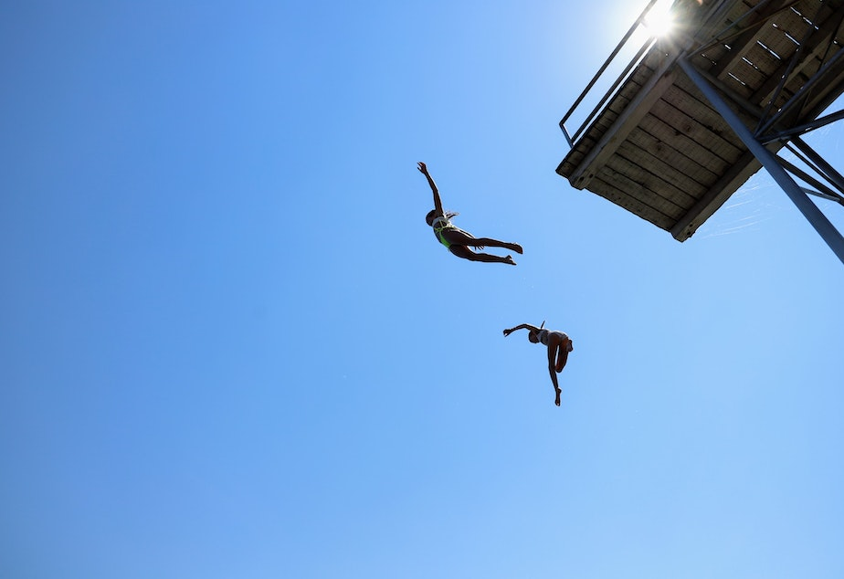 caption: Two people are jumping out of a platform in the Laurelhurst Beach Club June 28, 2021.