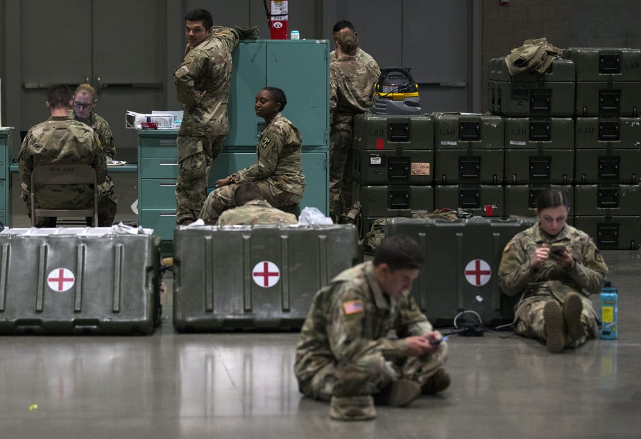 caption: U.S. Army soldiers are shown in the lab area of a military field hospital being deployed by soldiers from the 627th Army Hospital from Fort Carson, Colorado, along with soldiers from Joint Base Lewis-McChord on Tuesday, March 31, 2020, at the CenturyLink Field Event Center in Seattle. The 250-bed hospital will be for non COVID-19 patients.