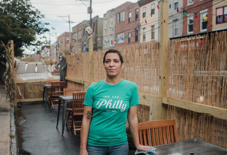caption: Danielle Renzulli, owner of 12 Steps Down Bar in Philadelphia, poses by the tables she has set up in what used to be parking spots. She was expecting some negative reactions from neighbors, given how valuable parking is in the area, but to her surprise, she received no complaints.