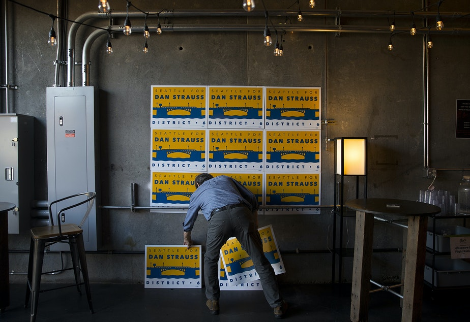 Robert Strauss arranges signs during a primary election night party in support of his son, Dan Strauss, a candidate for the Seattle city council in District 6 on Tuesday, August 6, 2019, at Obec Brewing in Seattle.