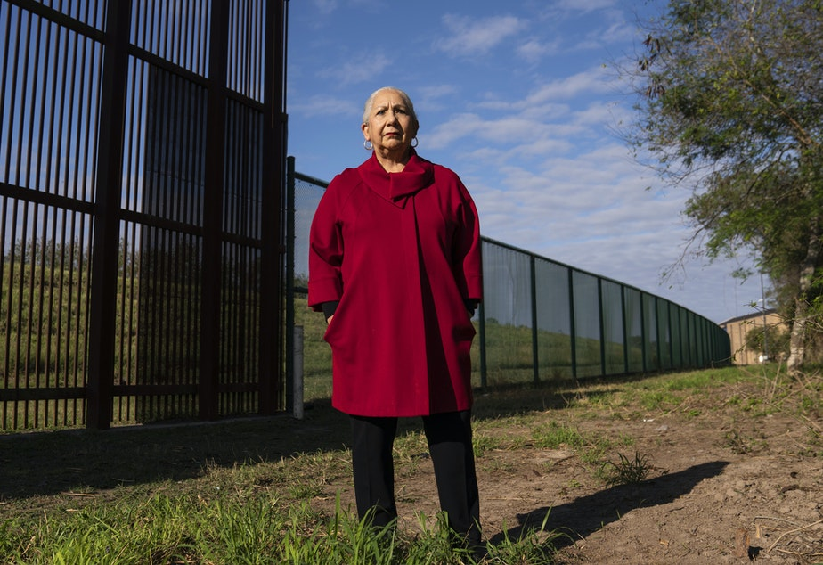 caption: Juliet García, former president of the University of Texas at Brownsville, stands behind the border wall.