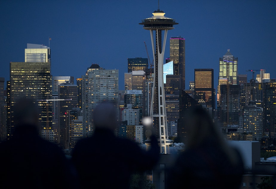 Crowds gather at 9:36 p.m. at Kerry Park on Monday, June 10, 2019, to watch the sun set over downtown Seattle. In these buildings, immigrant women are beginning their janitorial shifts, cleaning the city's high rises.