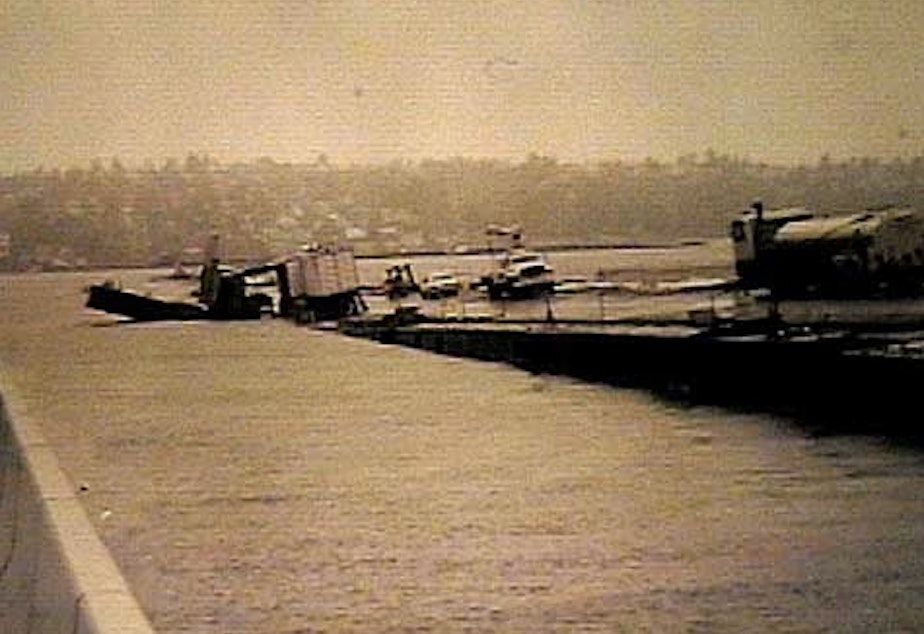 caption: The Lacey V. Murrow Floating Bridge across Lake Washington lists and sinks while undergoing renovation in November 1990.  No one was hurt, but several construction vehicles sank along with the old concrete pontoons.