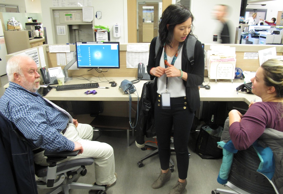 caption: Social worker, Huynh Chhor, speaks to mental health and social work staff in the Swedish Edmonds emergency department, February 25, 2019.