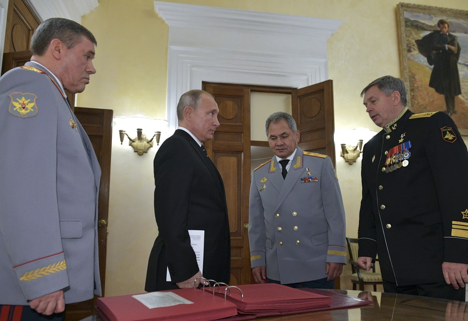 caption: Russian President Vladimir Putin (second from left) meets military officials, including Igor Kostyukov (far right), the deputy chief of military intelligence, the GRU. The 2018 event in Moscow marked the centenary of the GRU, which has been involved in many major operations in recent years. U.S. intelligence suspects of the GRU of involvement in a reported bounty program in Afghanistan.