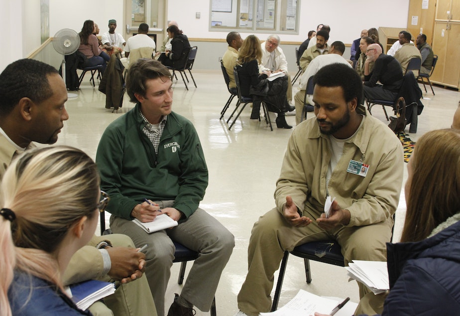 Teacher-in-training Mitch Ahmann (L) and others listen to Tony (R), a member of the Black Prisoners Caucus, at Monroe Correctional Complex on March 1, 2019.