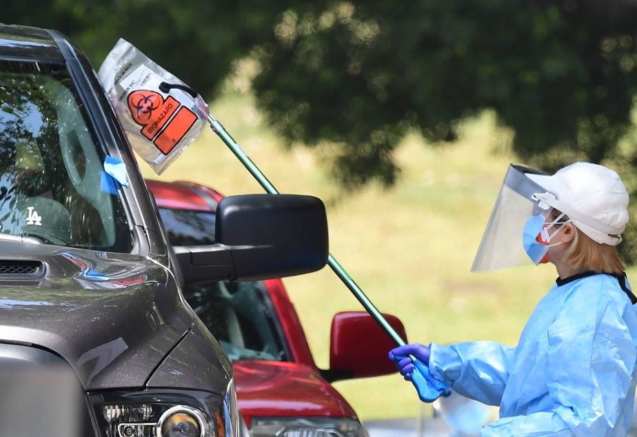 caption: A coronavirus test kit is handed to a driver in a vehicle at a testing site in Los Angeles on Wednesday.