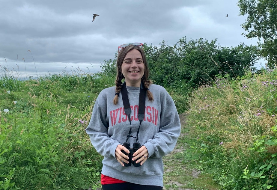 caption: Birder and Ph.D. candidate in avian research Olivia Sanderfoot poses near the Center for Urban Horticulture in Seattle, while swallows swoop in the background.