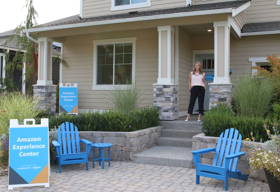 caption: Brittney Svach, a real estate agent, stands in front of an Amazon Smart Home in Black Diamond, Washington.