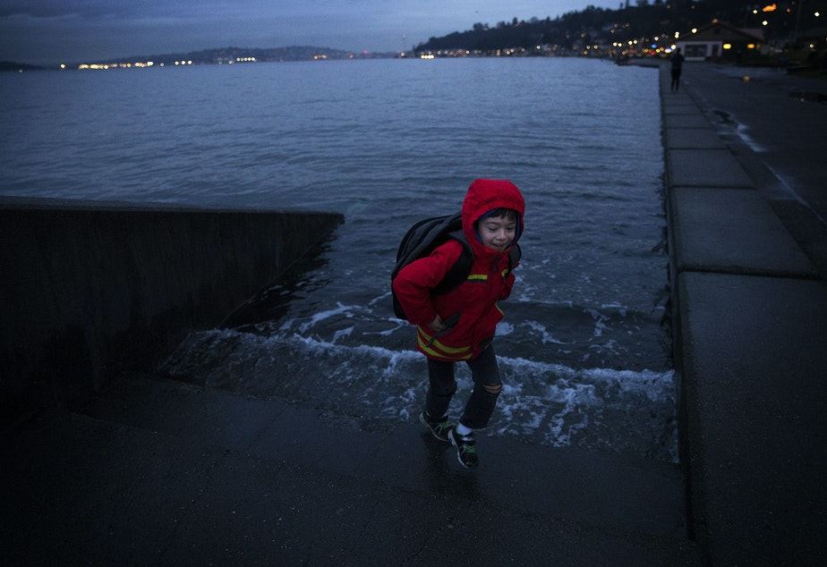 Ely Thomas, 7, runs from water spilling over a set of stairs  during a King Tide at Alki Beach Park on Friday, January 5, 2018, in West Seattle.