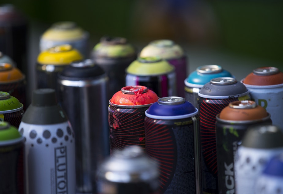 caption: A collection of spray paint is shown as artist Ryan Henry Ward works on a mural in the backyard of a home on Wednesday, September 8, 2021, in Shoreline.