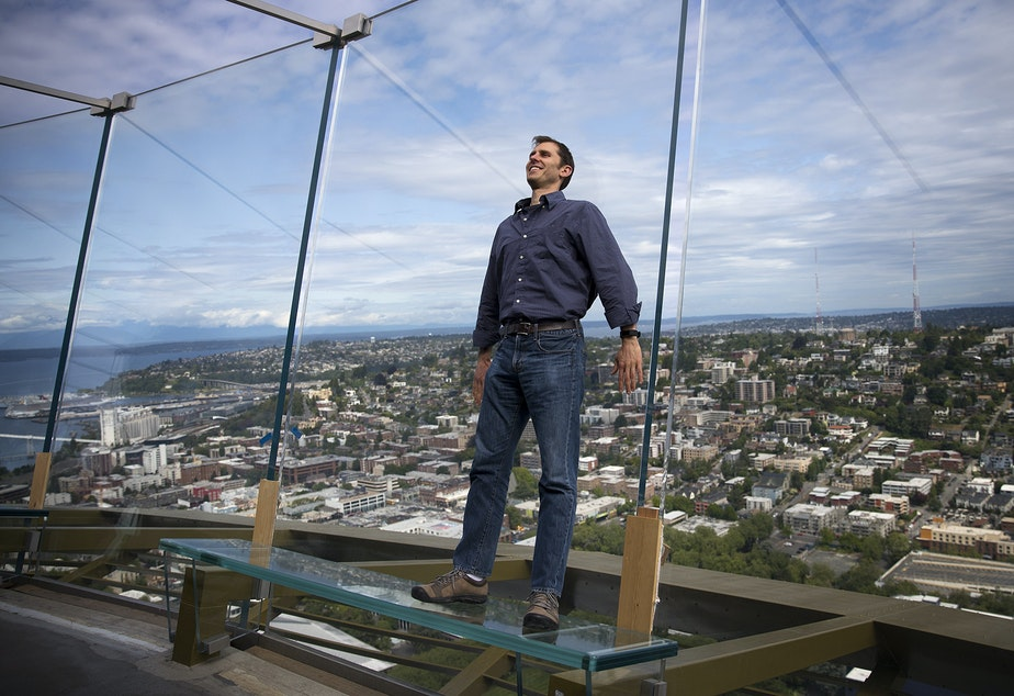 caption: Derek Hanson stands on a glass bench on the observation deck of the Space Needle on Tuesday, June 5, 2018, in Seattle. Hanson asked KUOW what would happen to the Space Needle in the event of an earthquake.