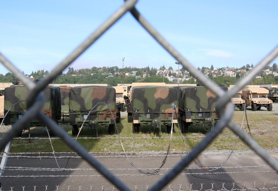 caption: The Washington National Guard's site in Seattle's Interbay neighborhood, seen through a fence at the edge of the Whole Foods parking lot.