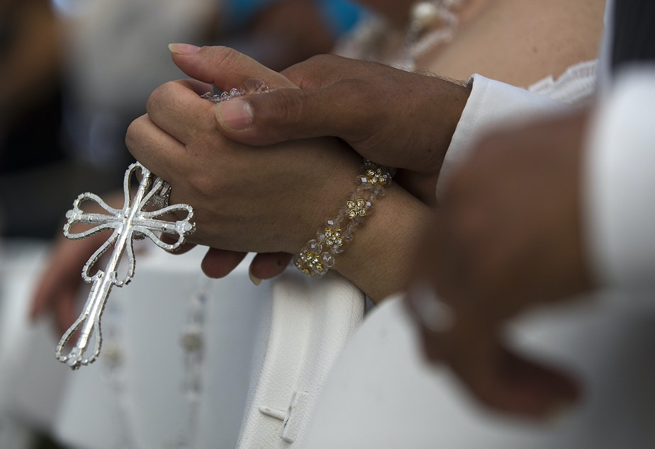caption: Ana Dely Morales and Ramon Sanchez Cordova hold a lasso de boda together during a mass wedding ceremony where they were married along with 22 other couples on Sunday, June 2, 2019, at Our Lady of the Desert Church in Mattawa.