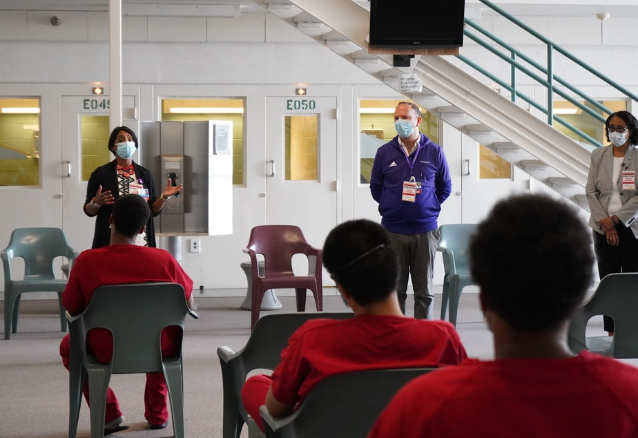 caption: Dr. Shireesha Dhanireddy, Dr. Santiago Neme and Dr. Bessie Young speak with inmates about the Covid vaccine at the Maleng Regional Justice Center on June 3, 2021.